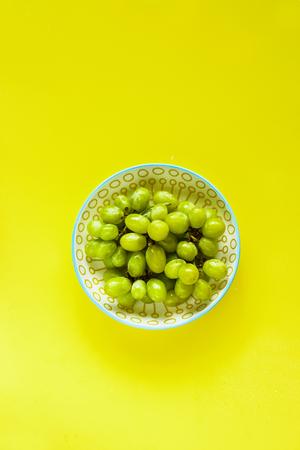 Fresh grape on yellow background flat lay