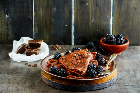 Homemade chocolate thin pancakes, crepes with fresh blackberries