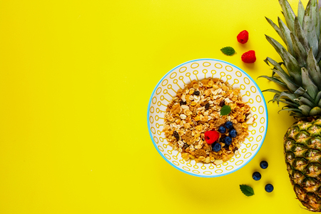 Muesli bowl, pineapple and fresh berries flat-lay. Healthy breakfast on yellow copy space background. Superfood and detox concept. Top view