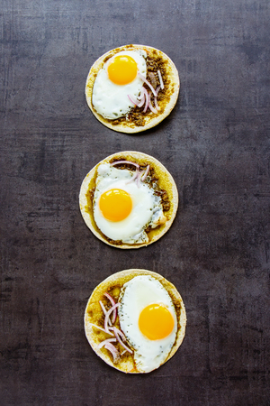 Corn tortillas with fried eggs, pesto sauce and onion flat lay