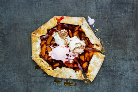 Plum pie or tart with ice cream close up. Seasonal Fall or Autumn dessert. Flat lay 写真素材