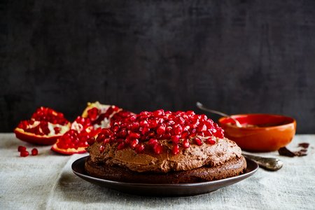 Homemade cake with chocolate mascarpone cream and fresh pomegranate