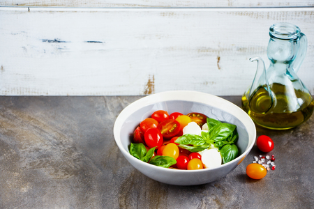 Italian caprese salad in bowl and ingredients. Tomato mozzarella basil leaves and olive oil. Italian cuisine. Mediterranean cuisine. Stock Photo