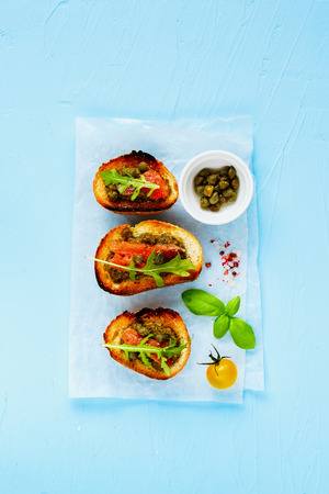 Toasts with smoked salmon, arugula, pesto sauce and capers flat lay