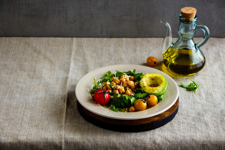 Chickpeas salad with arugula, avocado, cherry tomato and olive oil