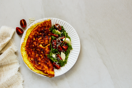 Healthy omelette with italian caprese salad and parmesan cheese flat-lay