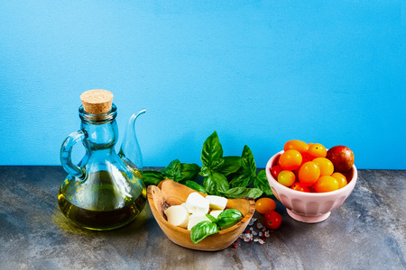 Italian salad. Mediterranean salad. Italian cuisine. Mediterranean cuisine. Tomato mozzarella basil leaves and olive oil on blue background Stock Photo
