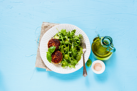 Homemade cutlets and salad on blue background flat lay