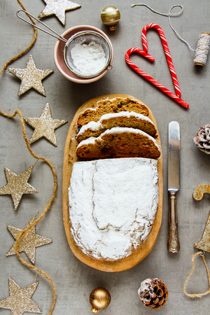 Christmas decorations and stollen cake flat lay. Traditional Dresdner christ pastry top view