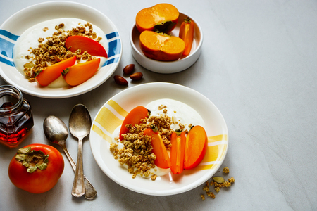 Flat lay of homemade granola, greek yogurt, fresh persimmon. Healthy seasonal fall breakfast Stock Photo
