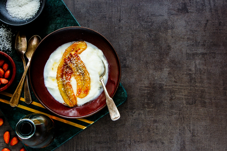 Flat lay of greek yogurt with grilled banana, coconut and maple syrup in breakfast bowl. Healthy food concept - Image