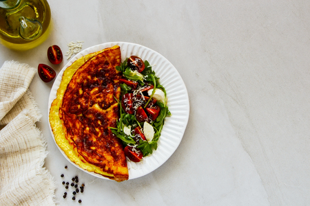 Flat-lay of omelette with italian caprese salad and parmesan cheese Stock Photo