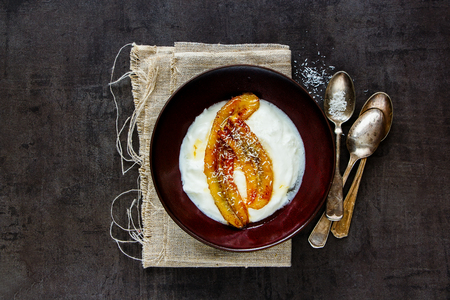 Greek yogurt with grilled banana, coconut and maple syrup in breakfast bowl flat lay. Healthy food concept - Image