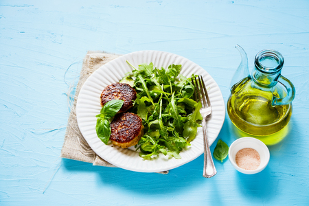 Tasty cutlets and green salad on blue background close up Imagens