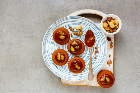 Flat-lay of caramel cookies with pishtachios on plate. Top view Stock Photo