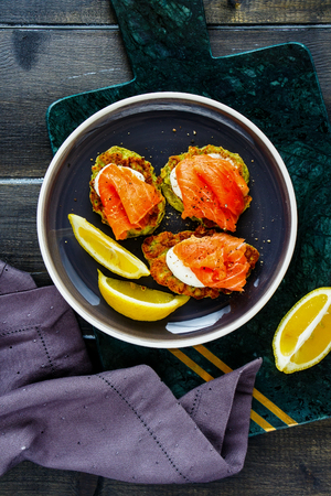 Healthy zucchini fritters with crème fraîche and smoked salmon flat lay