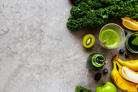 Making fresh green smoothie flat lay. Ingredients for making detox smoothie drink over grey concrete background - Image