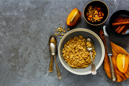 Flat-lay of cinnamon granola bowl, fresh persimmon and nuts over grey concrete table background, top view. Clean eating, dieting, vegetarian food - Image Stock Photo