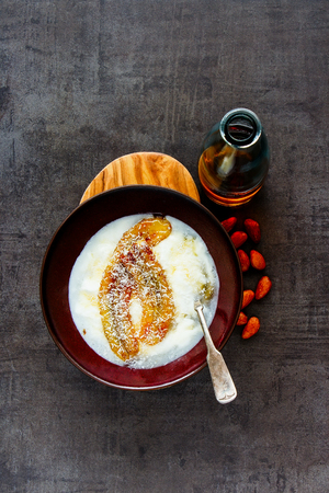 Flat- lay of greek yogurt with grilled banana, maple syrup and coconut in breakfast bowl. Healthy food concept - Image Stock Photo