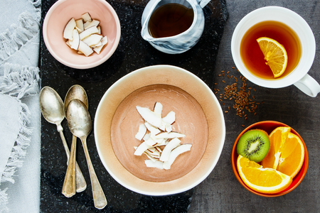 Flat-lay of tea cup, maple syrup, fresh fruits and chocolate yogurt bowl with coconut chips, top view. Sweet breakfast on concrete background - Image