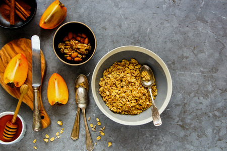 Flat-lay of healthy breakfast variety. Cinnamon granola bowl, fresh persimmon, honey and nuts over grey concrete table background, top view. Clean eating, dieting, vegetarian food - Image