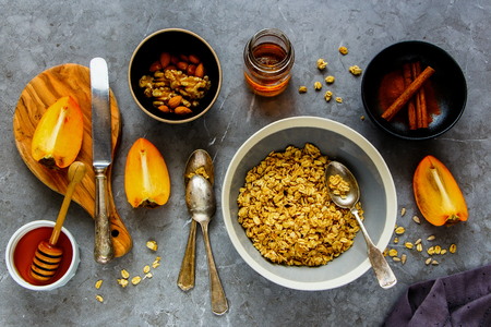Healthy breakfast variety flat lay. Cinnamon granola bowl, fresh persimmon, maple syrup, honey and nuts over grey concrete table background, top view. Clean eating, dieting, vegetarian food - Image