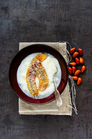 Bowl of greek yogurt with grilled banana, coconut and maple syrup flat lay. Healthy breakfast food concept - Image