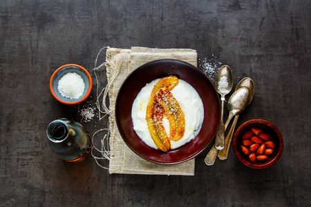 Breakfast bowl of greek yogurt with grilled banana, coconut and maple syrup flat lay. Healthy food concept - Image