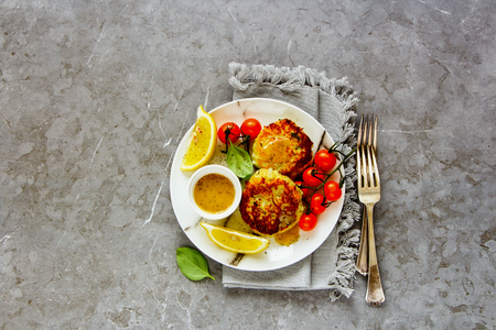Vegetarian cauliflower cakes with dip and vegetables flat lay Stock Photo
