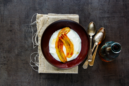 Greek yogurt with grilled banana and maple syrup in breakfast bowl flat lay. Healthy food concept - Image