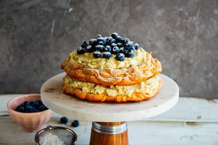 Meringue Pavlova cake on cake stand with fresh blueberry and mascarpone cream