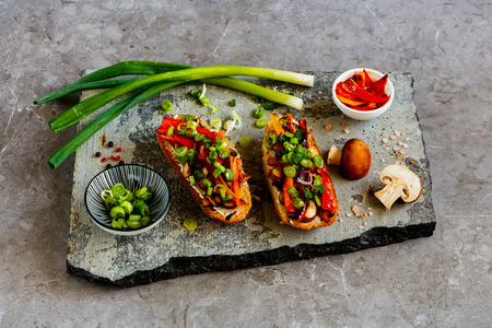 Hot mushroom toasts with grilled bell pepper on stone board close up Stock Photo