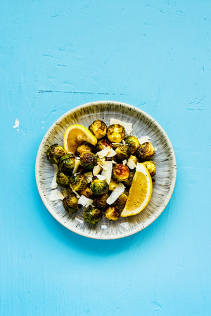 Fried Brussels sprouts with parmesan cheese on blue background flat lay