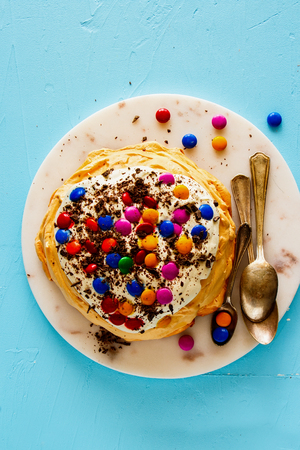 Flat-lay of Meringue Pavlova cake with colorful Sprinkles, whipped cream and chocolate on blue background