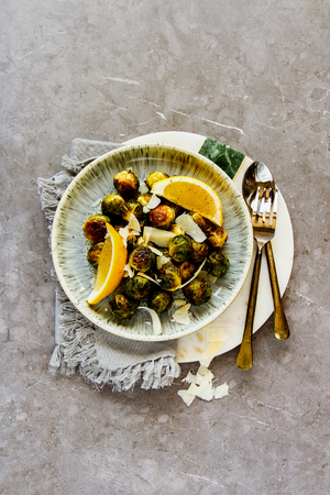 Fried Brussels sprouts with parmesan cheese in plate over rustic concrete background flat lay Stock Photo