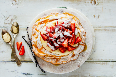 Vanilla Pavlova cake with strawberry and whipped cream flat lay top view