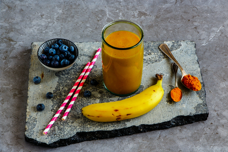 Jar of mango banana turmeric smoothie on stone board  Stock Photo