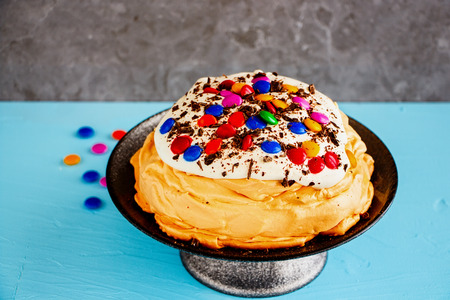 Close up of Meringue cake Pavlova with colorful Sprinkles, whipped cream and chocolate on cake stand Stok Fotoğraf