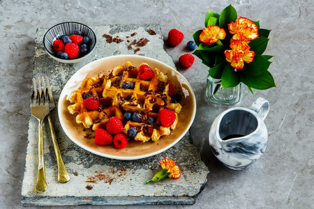 Breakfast, belgian waffles with berries and chocolate in plate close up