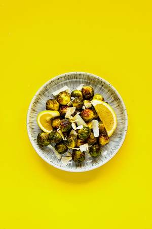 Fried Brussels sprouts with parmesan cheese on bright yellow background flat lay - Image
