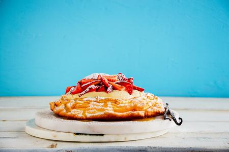 Pavlova cake with strawberry and whipped cream on blue background Stock Photo