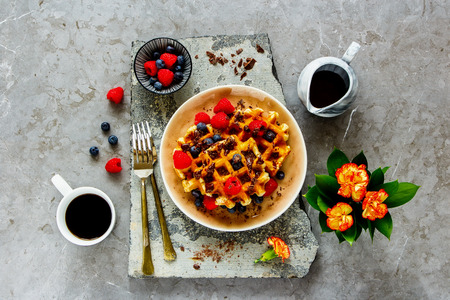 Breakfast, flat-lay of Belgian waffles, berries and coffee captured from above