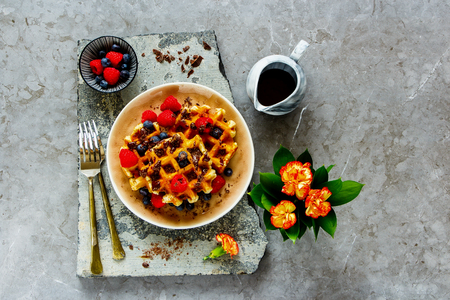 Belgian waffles with berries and chocolate on stone board captured from above, flat lay Banco de Imagens
