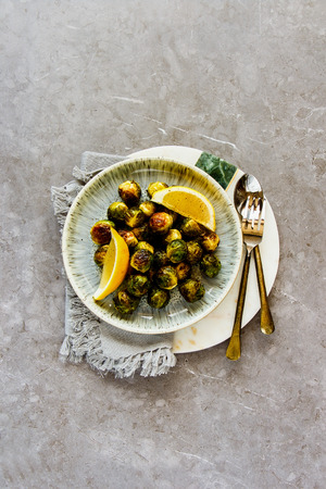 Fried Brussels sprouts in plate over rustic concrete background flat lay - Image Stock Photo