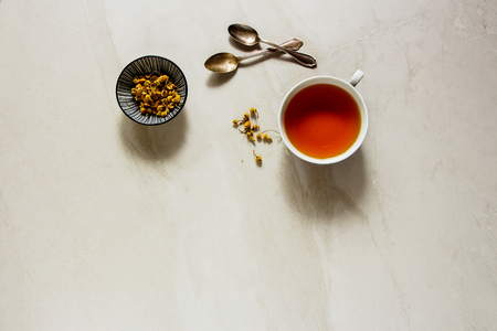 Chamomile tea in cup on vintage background flat lay. Tea composition from above Stock Photo