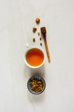 Chamomile tea on white board flat lay. Tea composition backgound from above