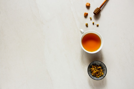 Chamomile tea on white board flat lay. Tea composition from above Stock Photo