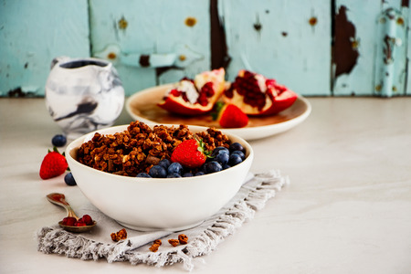 Delicious breakfast set with fruit, berry and chocolate granola on turquoise background close up
