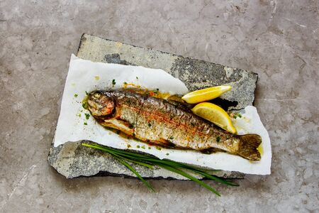 Flat-lay of Baked Trout Fish with Herbs and Lemon, top view 写真素材