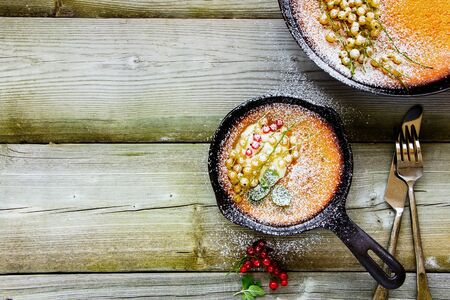 Homemade Danish pancake with red and white currant berries in frying pan, flat lay composition